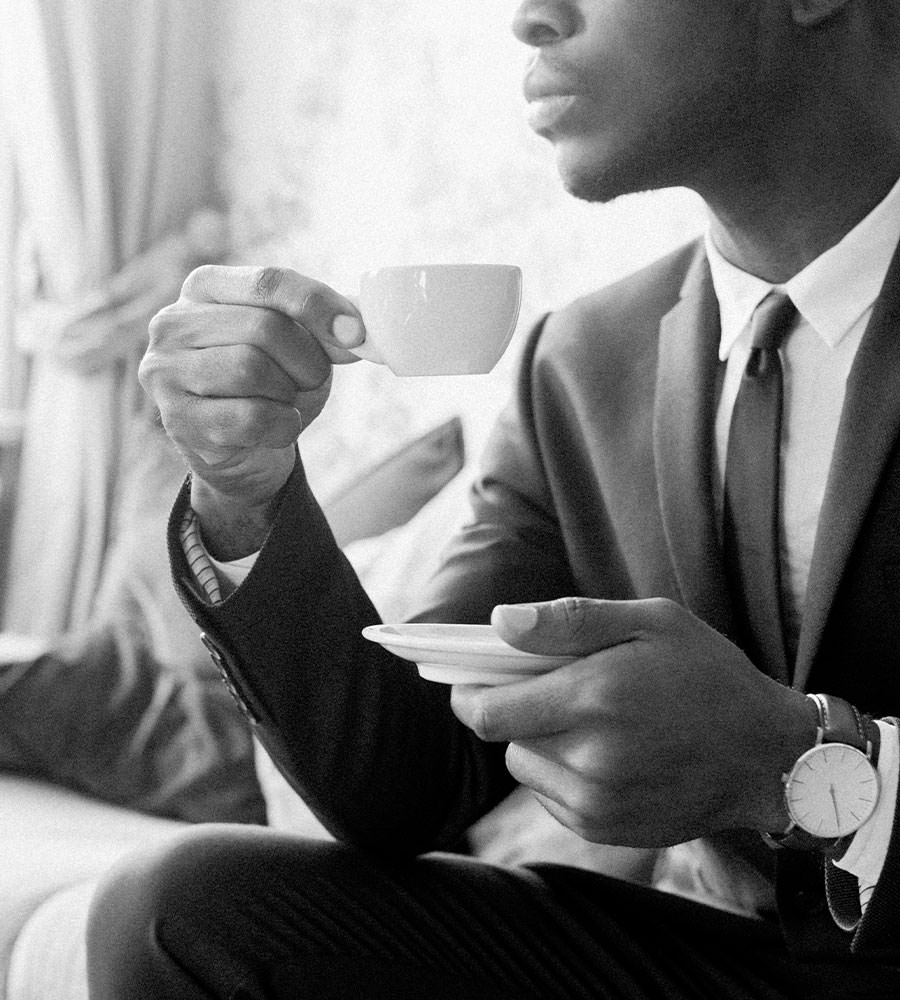 Man in a suit sipping coffee