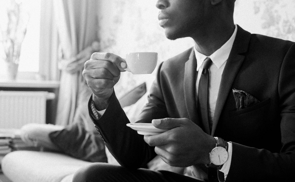 Man in a suit sipping espresso